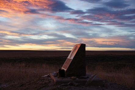 Memorial at SunsetBack lit clouds form an impressive backdrop to the stone memorial dedicated to the memory of the Sand Creek Massacre.