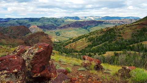 Four Bear TrailDeep red rocks stick up from bright green grassy hills.