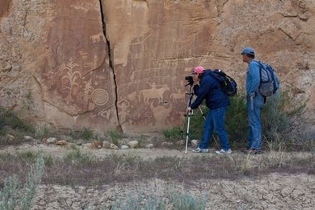 Crow Canyon PetroglyphsMan and woman photographing horse and character petroglyphs on the canyon wall.