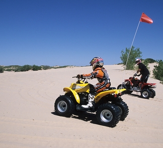 Mescalero Sands North Dune OHV AreaTwo all-terrain vehicle riders climbing a sand dune at Mescalero Sands North Dune Off-Highway Vehicle Area.