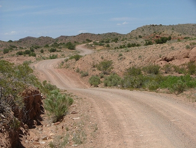 Quebradas Backcountry BywayA dirt road winds through sparsely vegetated hills.